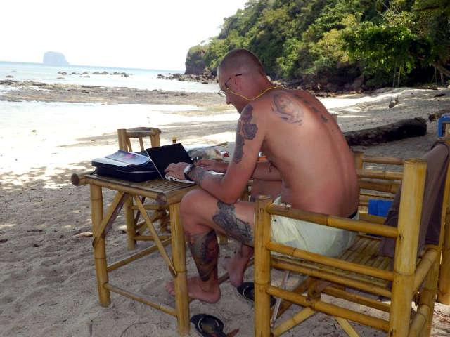 Bibo schreibt den Reisebericht am Strand von Koh Bulon