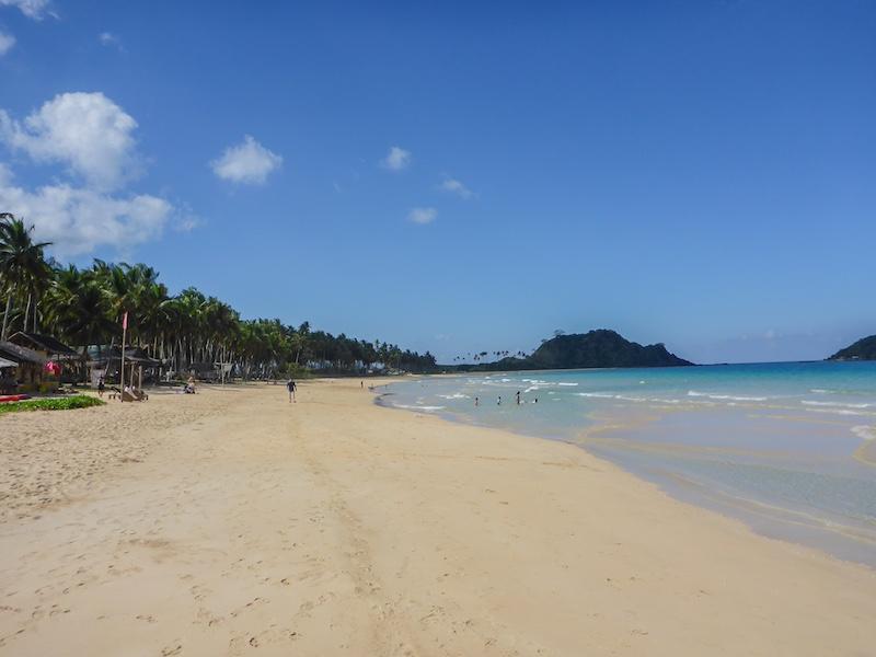 """Kurz vor dem Strand müssen wir uns registrieren und eine """"Tourism Develpoment Fee"""" von 100 PHP p.P. bezahlen, dann dürfen wir weiter. Ein herrlicher, langer Strand mit feinem Sand und traumhaften Badebedingungen hat uns empfangen und die Strapazen vergessen lassen! Aber in der Sonne liegen ist nicht, wir machen uns auf den Weg zum Viewpoint. Schon von Weitem kann man Personen auf einem Hügel sehen. Da müssen wir auch hin !"""